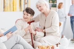 Happy grandmothers at day-care center. Volunteer reading a book to happy elderly women with a cane and her senior friend at day-care center Stock Photos