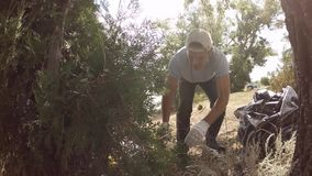 Volunteer removes debris in the forest, slow motion stock video footage