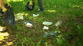 Volunteer scavenge plastic garbage in the summer park. Ecology concept