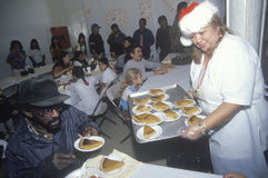 Volunteer serving pumpkin pie at homeless shelter for Christmas, Los Angeles, California Stock Image