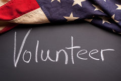Volunteer sign on a chalkboard. A volunteer sign on a chalkboard with a vintage American flag Royalty Free Stock Photo