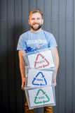 Volunteer with sorted waste. Male volunteer in blue t-shirt holding containers with sorted waste standing indoors on the gray wall background stock photo