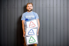 Volunteer with sorted waste. Male volunteer in blue t-shirt holding containers with sorted waste standing indoors on the gray wall background stock photos