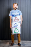 Volunteer with sorted waste. Male volunteer in blue t-shirt holding containers with sorted waste standing indoors on the gray wall background. Focused on the stock photos