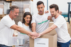 Volunteer team holding hands on a box of donations. In a large warehouse Royalty Free Stock Photography