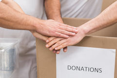 Volunteer team holding hands on a box of donations Stock Images