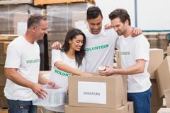 Volunteer team packing a food donation box. In a large warehouse Royalty Free Stock Photos