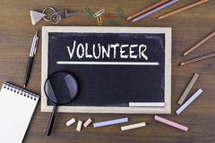 Volunteer. Text on the chalk board. Wooden table with a magnifying glass and writing utensils Stock Photos