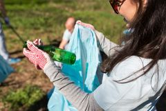 Volunteer with trash bag and bottle cleaning area Royalty Free Stock Photography