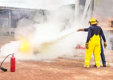 Volunteer using fire extinguisher from hose for fire fighting during basic fire fighting training evacuation. Volunteer using fire extinguisher from hose for stock photography