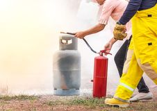 Volunteer using fire extinguisher from hose for fire fighting during basic fire fighting training. And fire drill evacuation royalty free stock photo