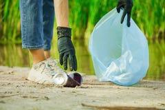 Volunteer woman puts a aluminium can in a trash bag
