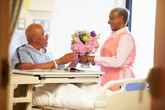 Volunteer Worker Tidying Male Patient's Hospital Room. Giving Bunch Of Flowers Stock Photography