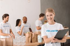 Volunteer writing in clipboard Royalty Free Stock Photography