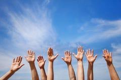 Volunteering concept, hands of group of people. Volunteers in blue sky royalty free stock images