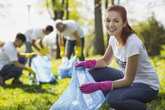 Happy female volunteer serving nature. Volunteering in park. Joyful female volunteer grinning while gathering rubbish royalty free stock photos