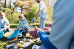 Volunteer with trash bag and bottle cleaning area Royalty Free Stock Images