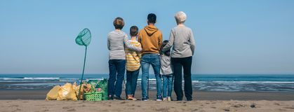 Volunteers backwards watching the sea. Group of volunteers backwards watching the sea after cleaning the beach royalty free stock images