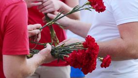 Men handing out flowers for put them to monument in memory of falling people. Volunteers with carnation red flowers on memorial day in square. Men handing out stock footage