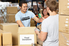 Free Volunteers Collecting Food Donations In Warehouse Royalty Free Stock Image - 29350196