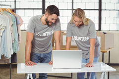 Volunteers discussing while working on laptop in office Royalty Free Stock Photos