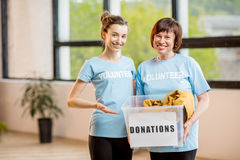 Volunteers with donation box. Young and older volunteers dressed in blue t-shirts holding container with donations of clothes indoors at the office royalty free stock photography