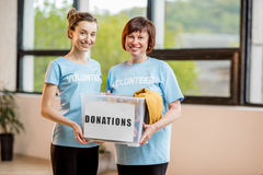 Volunteers with donation box. Young and older volunteers dressed in blue t-shirts holding container with donations of clothes indoors at the office Stock Photography