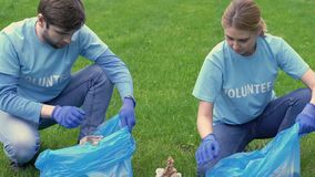 Volunteers family collecting rubbish in park, giving high-five, eco project. Stock footage stock video
