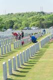 Volunteers and family members place flags on fallen heroes heads royalty free stock images