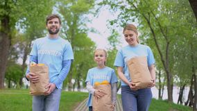 Volunteers family walking park holding paper bags with apples and oranges, help stock video