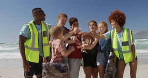 Volunteers forming hand stack on the beach 4k. Front view of diverse volunteers forming hand stack on the beach. They are smiling 4k stock footage