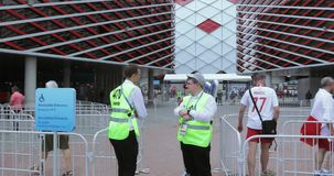 Volunteers in front of football. Russia, Moscow - June 19, 2018: Football fans of Poland, Senegal, Russia before the match Poland - Senegal at the stadium stock footage