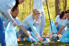 Volunteers with garbage bags cleaning park area Stock Images