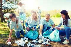 Volunteers with garbage bags cleaning park area. Volunteering, charity, people and ecology concept - group of happy volunteers with garbage bags cleaning area in Royalty Free Stock Photo