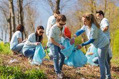 Volunteers with garbage bags cleaning park area. Volunteering, charity, cleaning, people and ecology concept - group of happy volunteers with garbage bags stock images