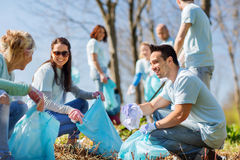 Volunteers with garbage bags cleaning park area Royalty Free Stock Photos