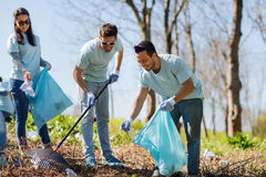 Volunteers with garbage bags cleaning park area Royalty Free Stock Photography