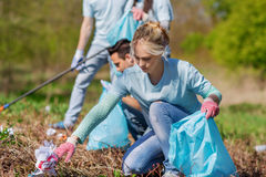 Volunteers with garbage bags cleaning park area Stock Image