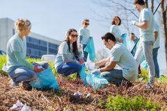 Volunteers with garbage bags cleaning park area Royalty Free Stock Photo
