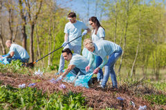 Volunteers with garbage bags cleaning park area Royalty Free Stock Images