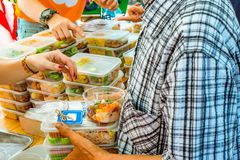 Volunteers giving food to poor people. Poverty concept. Private enterprise charities give food to the underprivileged Royalty Free Stock Image