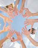 Volunteers with hands together against blue sky Royalty Free Stock Images