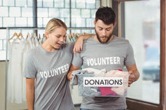 Volunteers looking at clothes in box Stock Image