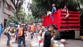 Volunteers and municipal workers work together by the earthquake. Volunteers and municipal workers work together to remove debris caused by the earthquake in stock video footage