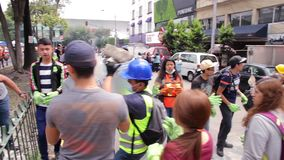 Volunteers and municipal workers work together by the earthquake. Volunteers and municipal workers work together to remove debris caused by the earthquake in stock footage