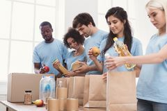 Volunteers packing food and drinks into paper bags. Volunteers office, group of people sorting food for charity, copy space royalty free stock image