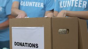 Volunteers packing clothes in box for donations, low-income families assistance. Stock footage stock footage