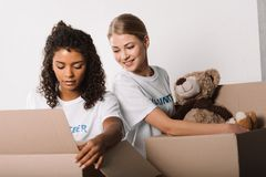 Volunteers packing toys for charity. Beautiful female volunteers packing toys for charity Royalty Free Stock Photos