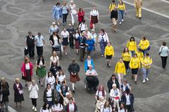 Volunteers and pilgrims in Lourdes France. LOURDES, FRANCE - JULY 6, 2016: Dozens of volunteers and pilgrims, some in wheelchairs, at the Shrine of Our Lady of stock photo