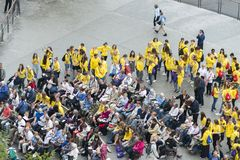 Volunteers and pilgrims in Lourdes France. LOURDES, FRANCE - JULY 6, 2016: Volunteers and pilgrims, waiting for the mass to begin, near the Shrine of the Virgin stock photo